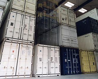 Stacked shipping containers in a warehouse.