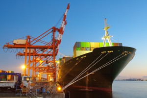 Container Cargo freight ship with working crane bridge