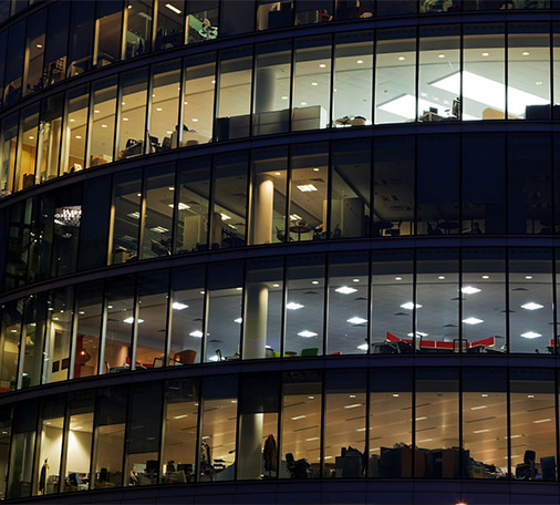 Front of office-building windows at night.